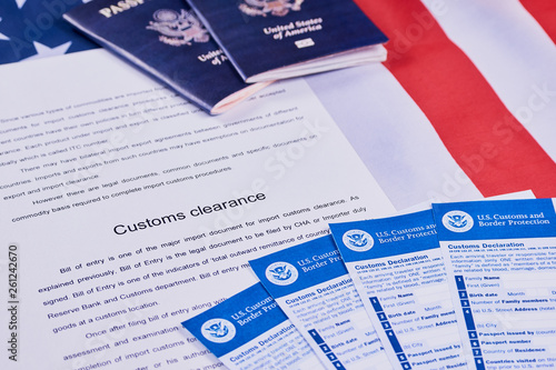 Fotomural  Page of paper with words Customs Clearance next to American passports and Forms