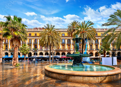 Poster Barcelona Royal area in Barcelona, Spain. Fountain with statues and high palm trees among traditional Spanish architecture at main central square of old town. Summer landscape with blue sky and clouds.