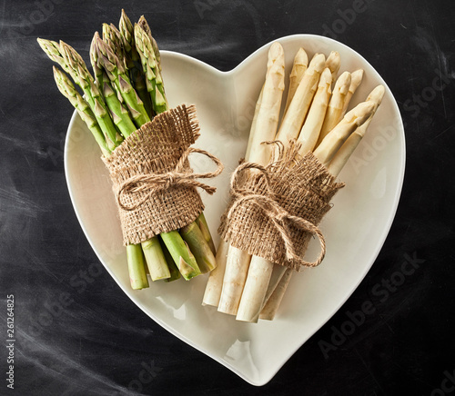 Heart shaped bowl with fresh asparagus spears