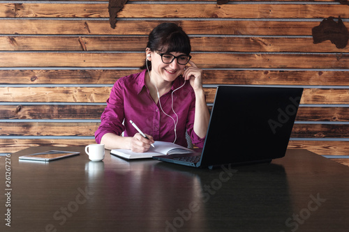 Vászonkép Smiling businesswoman listening to music at work