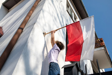 The boy is hanging a flag. Polish National Day of the Third of May, Constitution Day Flag Day, International Labor Day