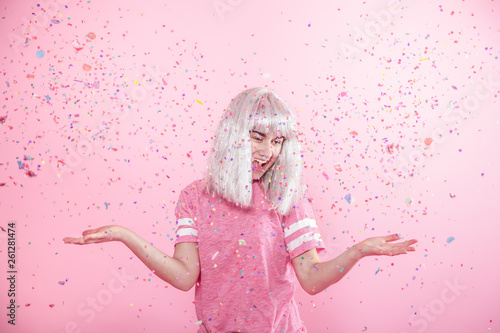 Photo sur Toile Carnaval Funny Girl with silver hair gives a smile and emotion on pink background. Young woman or teen girl with confetti