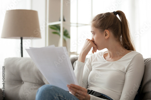 Fotografía Upset thoughtful woman holding paper document in hands, sitting on sofa