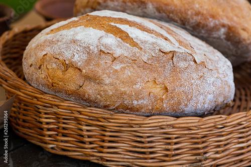 Fotografie, Obraz  loaf bread round fresh delicious whole-grain brown in a wicker basket close-up