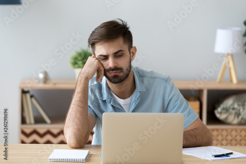 Tired student or employee working with laptop, doing boring job Canvas Print