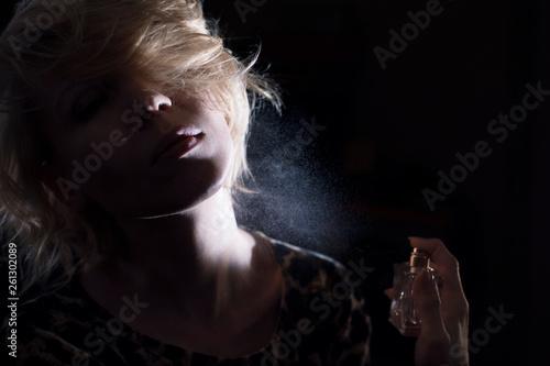 Fotografía  Woman puts on perfume on a dark background.