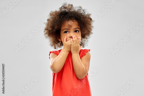 Fototapeta childhood, expression and emotion concept - confused little african american girl covering mouth by hands over grey background obraz na płótnie