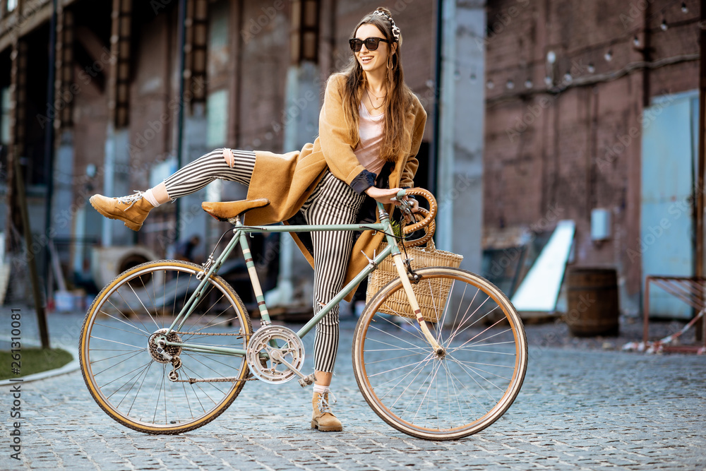 Fototapety, obrazy: Full body portrait of a beautiful stylish woman dressed in coat standing with retro bicycle outdoors on the industrial urban background