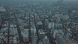 Aerial drone panning directly above the bustling city of Tokyo full of roads, cars, buildings, a canal, offices and skyscrapers on an overcast cloudy day