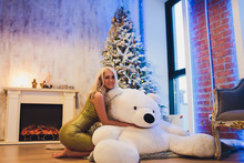 Fashion Interior Photo Of Beautiful Gorgeous Woman With Blond Hair In Luxurious Dress Posing In Room With Christmas Tree And Decorations.