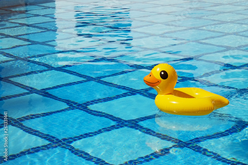 Photographie Top view of inflatable duck floating in an empty swimming pool with crystal clear water and blue square tile pattern background