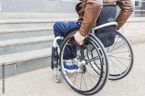 Valokuva  Man in wheelchair in front of stairs.