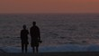 Silhouette of a couple on the beach at sunset.