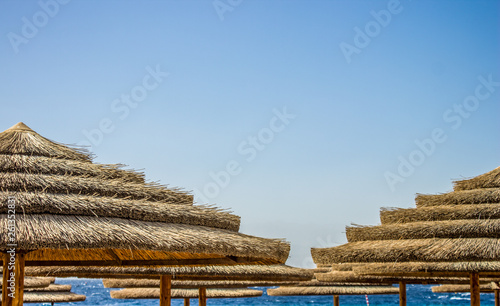 Foto  straw umbrella in beach summer vacation outdoor concept photography with blue sk