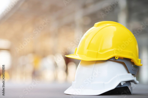 Obraz yellow and white hard safety wear helmet hat in the project at construction site building on concrete floor on city with sunlight. helmet for workman as engineer or worker. concept safety first.  - fototapety do salonu