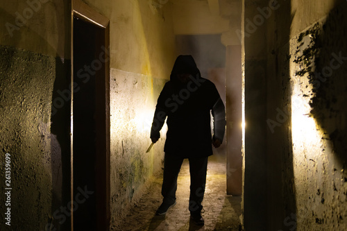 Photo Creepy silhouette with knife  in the dark abandoned building