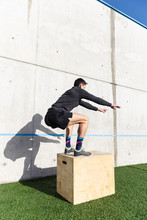 Side View Of Young Athletic Male Jumping On Box Near Grey Wall In Sunny Day