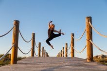 Young Ballerina In Black Wear With Upped Leg In Air On Footbridge And Blue Sky In Sunny Day