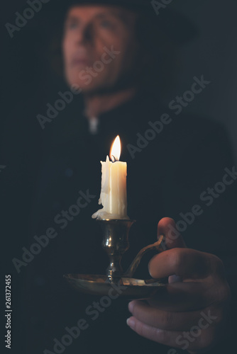 Photographie  Mysterious victorian priest in black coat and hat holding candlestick