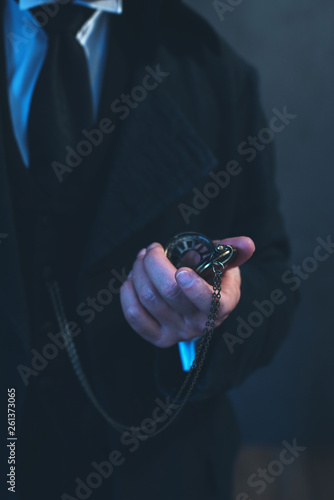 Edwardian man in long black coat holding pocket watch. Poster Mural XXL