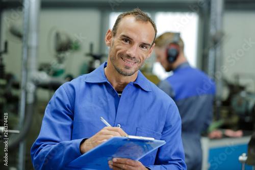 portrait of factory supervisor holding clipboard Fototapeta