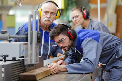 carpenter training female apprentice to use plane Canvas Print