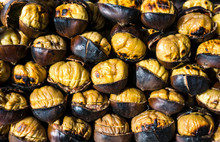 Fried Chestnuts On Street. Traditional Street Food In Winter Fire. Roasted Chestnut Background. Nutrition, Agriculture, Harvest Concept. Bunch Of Hot Fresh Delicious Grilled Chestnuts At Street Vendor