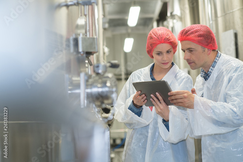two quality control workers wearing hairnets looking at digital tablet Wallpaper Mural
