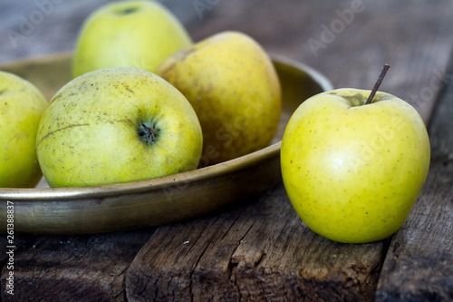 Fotografía  Fresh yellow-green apples lie in an old-fashioned brass plate on an old, textural, rustic table, soft focus