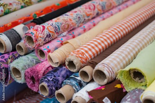 Pinturas sobre lienzo  many fabric rolls and colorful textiles at market