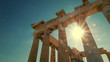 Sun shines between the columns of the Parthenon at the Acropolis in Athens, Greece