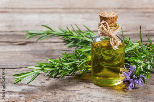 Fototapeta Top view Bottle glass of essential rosemary oil with rosemary branch and flower on wooden rustic background. herbal oil concept, Rosmarinus Officinalis obraz