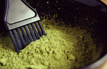 Macro Of Green Natural Henna Powder In A Bowl With Black Brush. Organic Care And Eco Dye For Hair. Dried Lawsonia Inermis As Colorant.