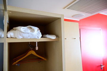 Fototapeta na wymiar Open closet with hangers in the hotel room