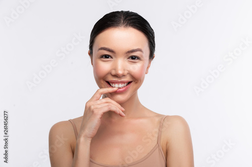 Fototapeta Dark-eyed woman wearing beige camisole smiling broadly
