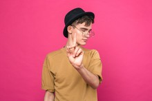 Portrait Of A Disgruntled Young Guy On A Pink Background Waving His Finger In Front Of Him Denying The Obvious