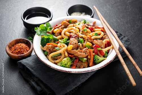 Photo  Udon stir fry noodles with pork meat and vegetables in a white plate on black stone background