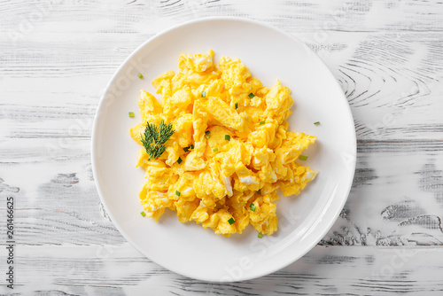 Photo Scrambled eggs on white plate over white wooden background.