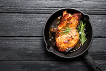 Fried Pork Steak In Frying Pan On Black Wooden Background.