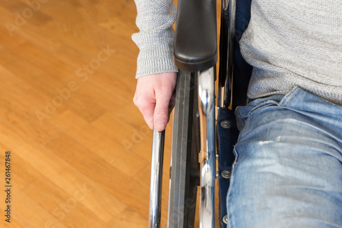 Fotografiet  Detail of disabled man hand holding wheel of a wheelchair.