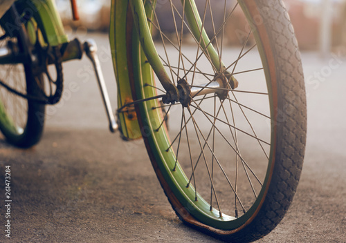Aluminium Prints Bicycle Beautiful retro bike green, standing on the asphalt with a flat tire on the wheel and illuminated by the sun
