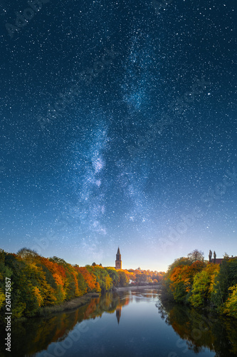 Fotografia  Ethereal image of fall foliage and Aura river with Turku Cathedral in Finland against beautiful milky way on the sky