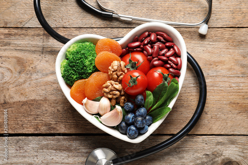 Fototapeta Bowl with products for heart-healthy diet and stethoscope on wooden background, top view obraz