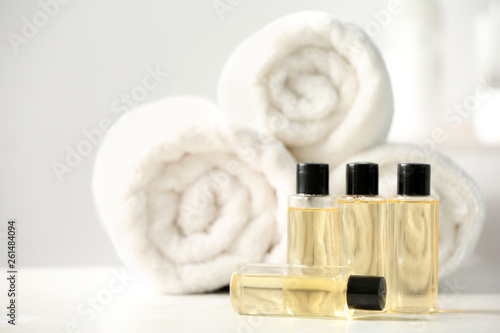 Photo Mini bottles with cosmetic products and towels on table, space for text