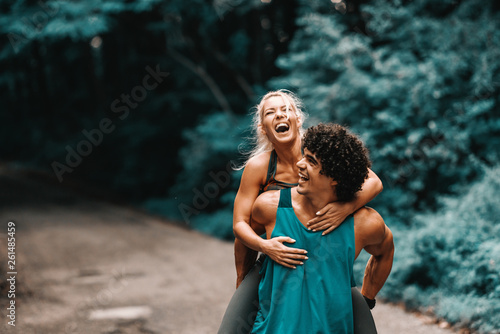 Fotografía  Happy sporty Caucasian couple having piggyback in nature in summertime