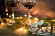 Leinwanddruck Bild - Closeup of red wine on table with Christmas lights. Christmas table and tree.