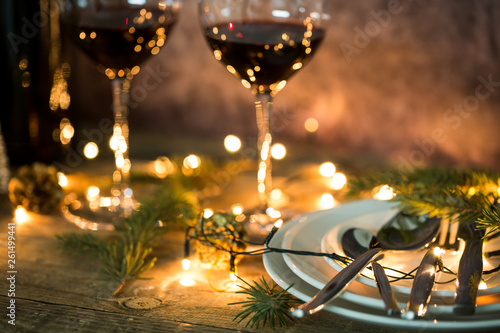 Acrylic Prints Wine Closeup of red wine on table with Christmas lights. Christmas table and tree.