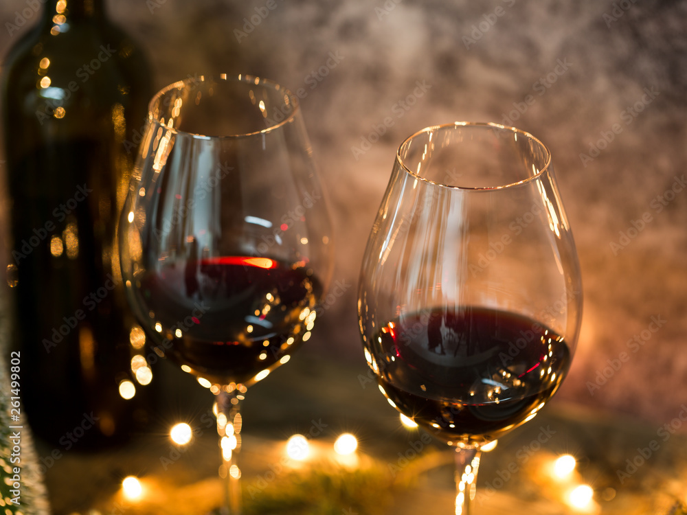 Fototapety, obrazy: Red wine on table with Christmas lights on the background