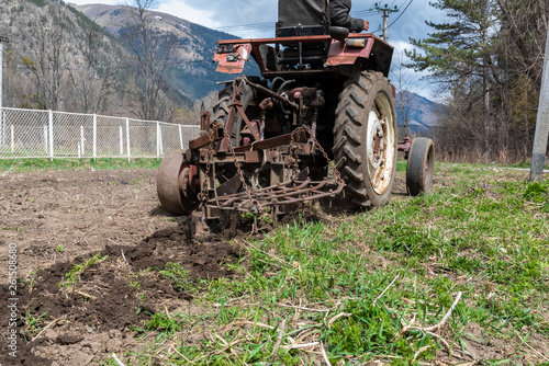 Photo Stands Motor sports old small tractor harrow field in spring, Caucasus. Karachay-Cherkessia Russia