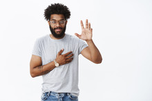 You Have My Word. Portrait Of Charming Confident, Smiling African American Man Giving Promise Raising Hand And Holding Arm On Heart As Giving Oath Or Pledge, Swearing Not Lie Over Gray Background
